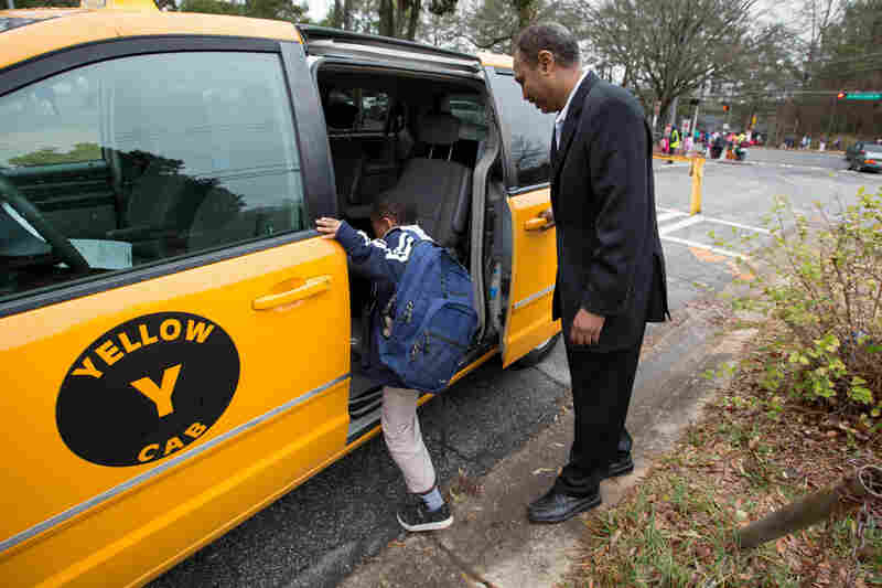 Most days, Shekhey uses his taxi to help transport refugees who have no other transportation and to shuttle children to an after-school program he runs at a local church. Here, he picks up Milkeso Sayida, 8, from Indian Creek Elementary School.
