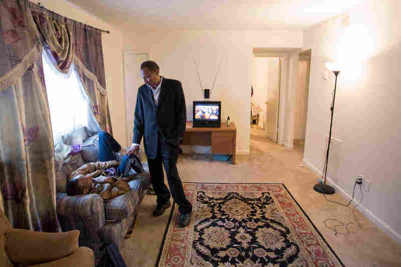 """Shekhey talks with a disabled Somali who recently arrived in the United States in the apartment where the man lives with other Somali refugees. """"Communities have to help each other,"""" Shekhey says. """"That's the way we build dreams."""""""