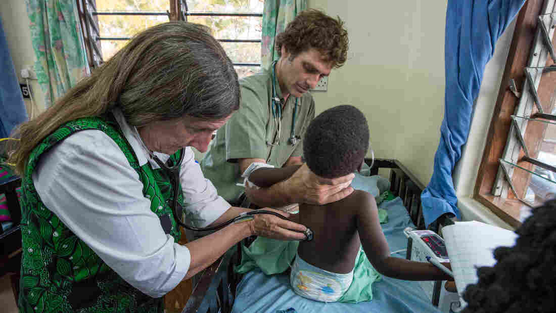 Dr. Terrie Taylor, left, and Dr. Karl Seydel take a child's vitals in the malaria ward at Queen Elizabeth Hospital in Blantyre, Malawi.