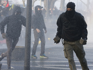 A protester holds a stone as police use water cannons on crowds near the new headquarters of the European Central Bank in Frankfurt, Germany.