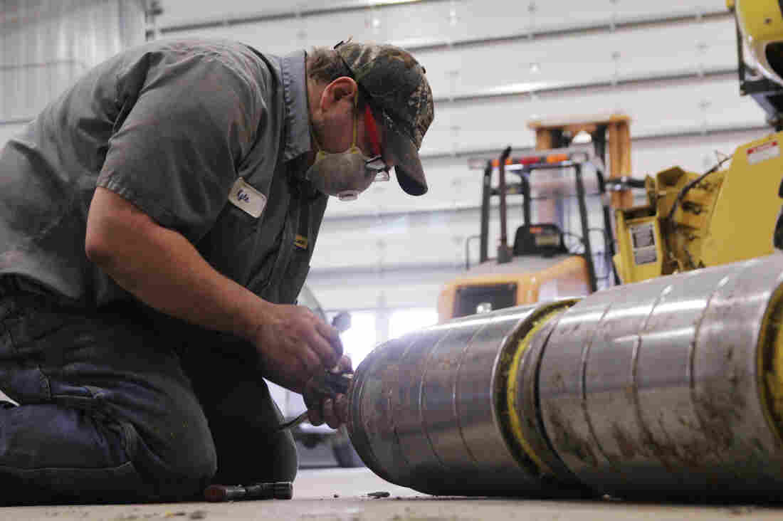 Kyle Garman, a technician at the the New Holland dealership in East Havana, Ill., takes apart the feeder head on a large combine. Owner Frank Hofreiter says farm customers are opting to repair old equipment rather than buy new.