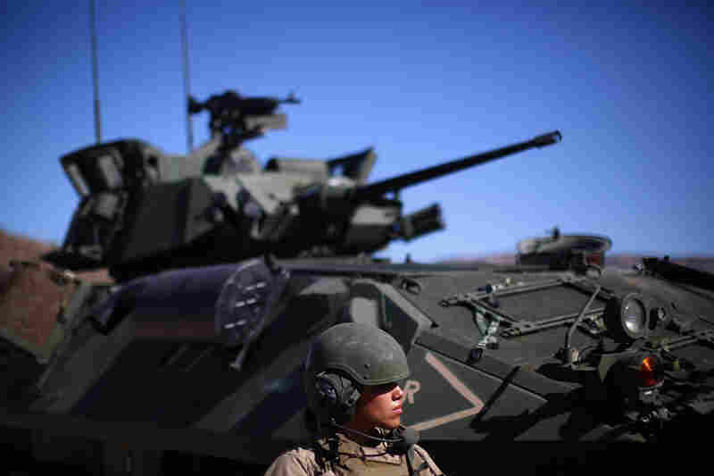 Marine Lance Cpl. Paula Pineda stands in front of a light armored vehicle, or LAV, during an exercise at Twentynine Palms in the Mojave Desert.