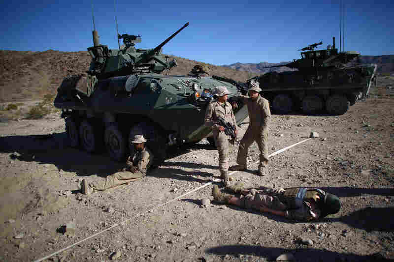 """Marines wait with """"Carl,"""" a 220-pound dummy that acts as a stand-in for a wounded Marine during the exercise."""