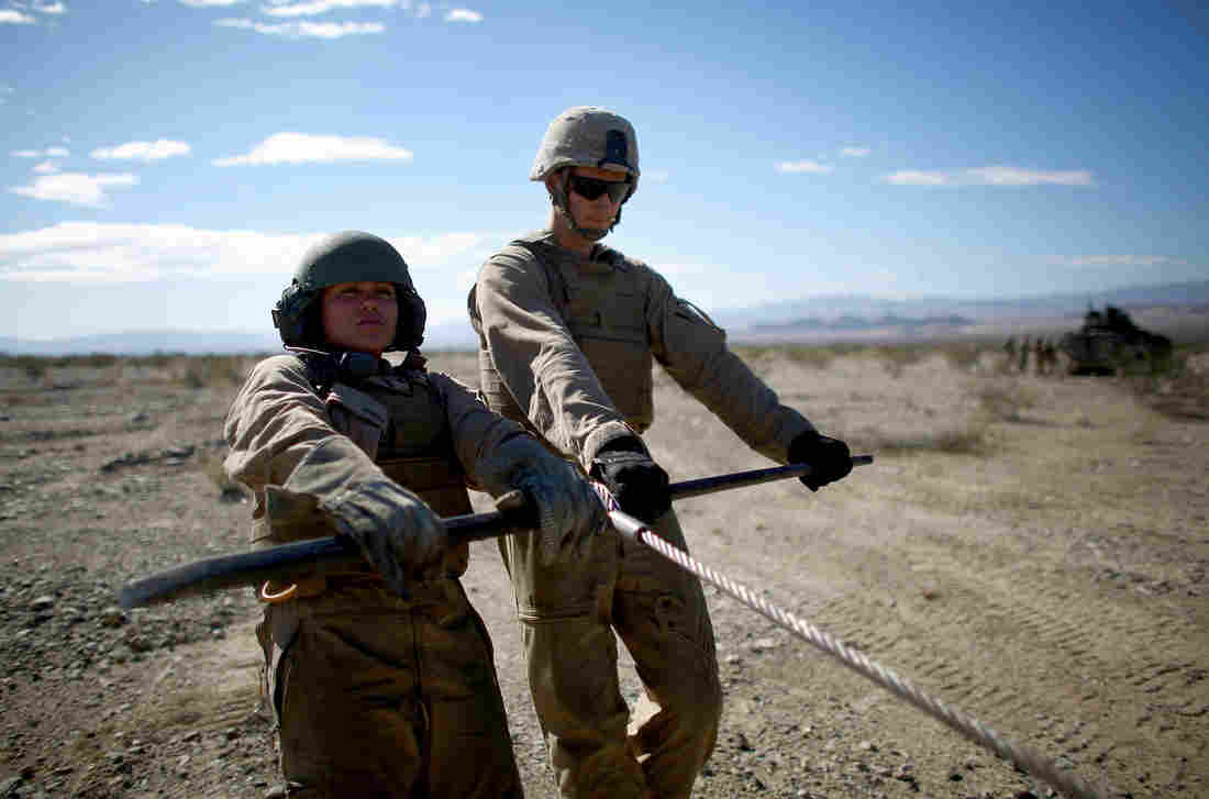 Marine Lance Cpl. Paula Pineda (left) and Cpl. Ryan Donk pull out a winch cable for a vehicle towing exercise.