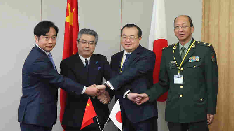 Liu Jianchao (second right), China's assistant foreign minister, shakes hands with Japanese Deputy Foreign Minister Shinsuke Sugiyama (second left) during a meeting in Tokyo, Japan on Thursday.