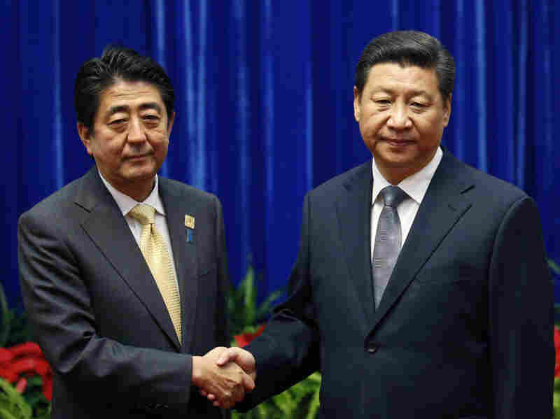 Japan's Prime Minister Shinzo Abe, left, and China's President Xi Jinping, right, shake hands during their meeting at the Great Hall of the People, on the sidelines of the Asia-Pacific Economic Cooperation (APEC) summit in November.