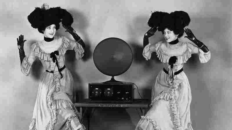 Ladies in long dresses practice polka steps by a radio, circa 1920s.