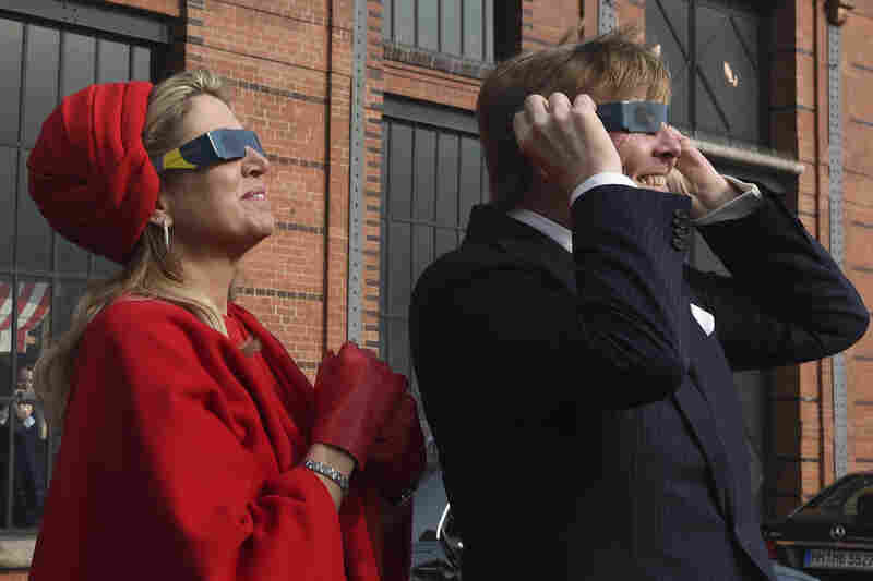 Dutch King Willem-Alexander and Queen Maxima wear protective glasses as they watch the partial solar eclipse in Hamburg, Germany.