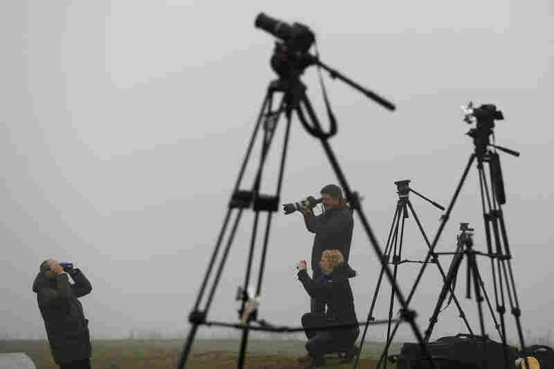 "Journalists prepare to view the partial eclipse at the ""Halde Hoheward"" in the western city of Herten, Germany."