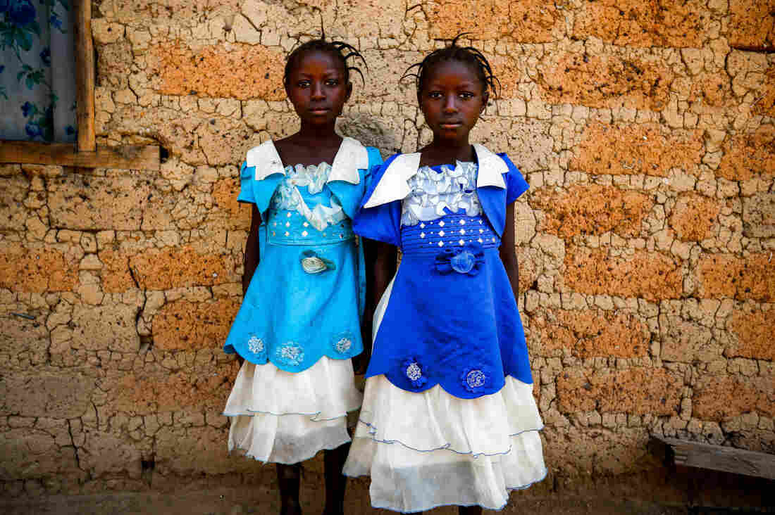 Twins Watta and Fatta Balyon pose outside the home of their guardian Mamuedeh Kanneh in Barkedu, a village in Liberia.
