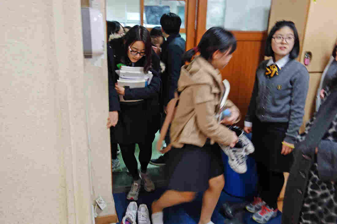 Students take off their shoes before entering the study hall.