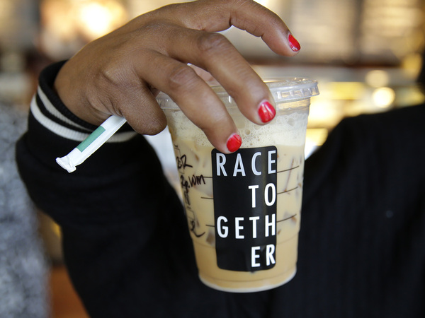 """Larenda Myres holds an iced coffee drink with a """"Race Together"""" sticker on it at a Starbucks store in Seattle. Starbucks baristas will no longer write """"Race Together"""" on customers' cups starting Sunday."""
