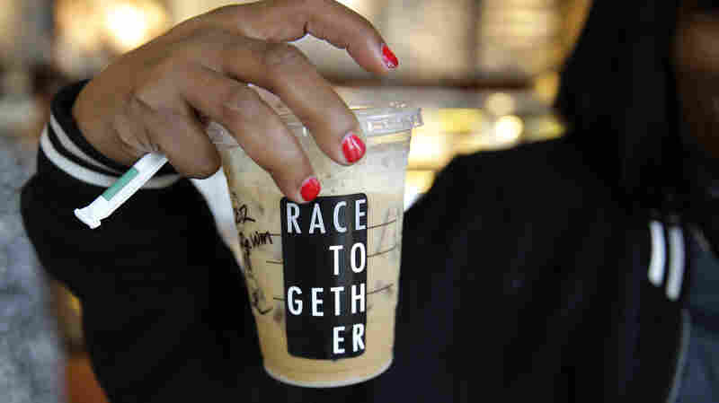 "Larenda Myres holds an iced coffee drink with a ""Race Together"" sticker on it at a Starbucks store in Seattle. Starbucks baristas will no longer write ""Race Together"" on customers' cups starting Sunday."