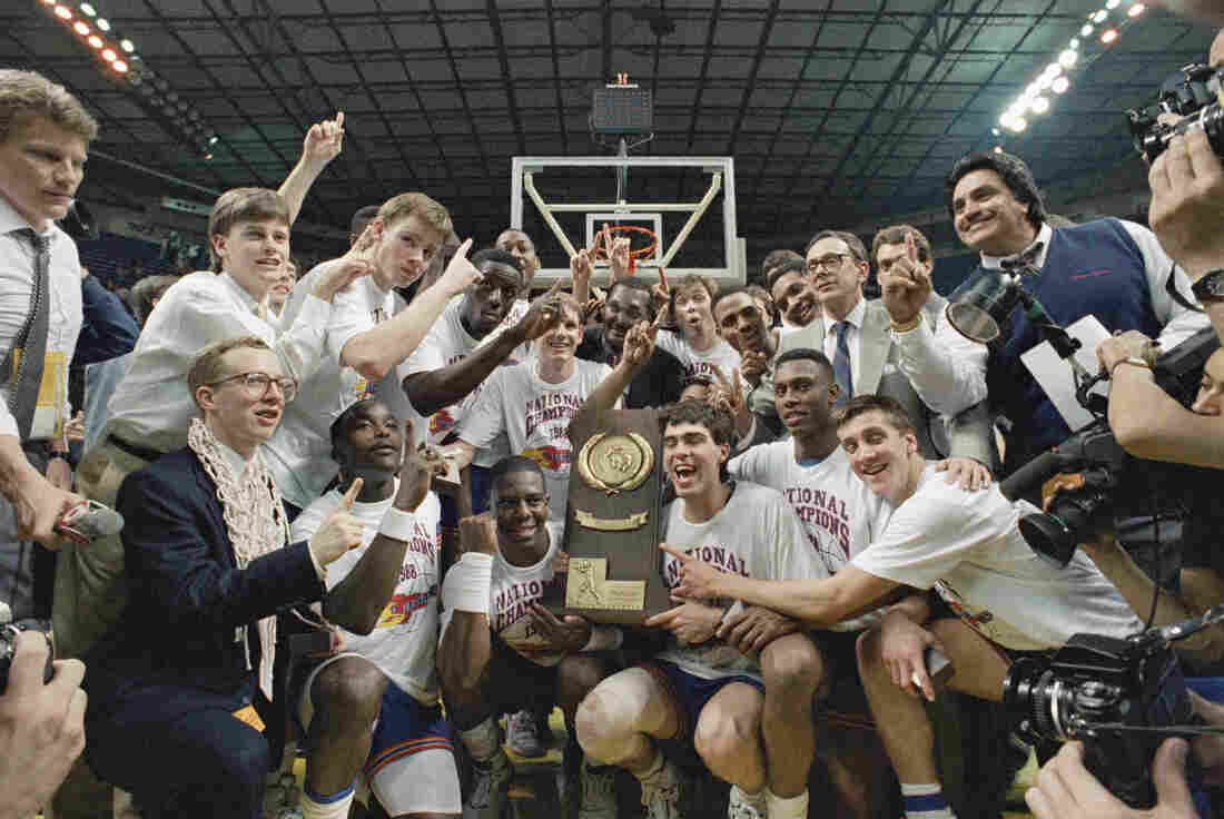 The 1988 Kansas Jayhawks hold up their trophy after winning the championship game of the NCAA Final Four Tournament.