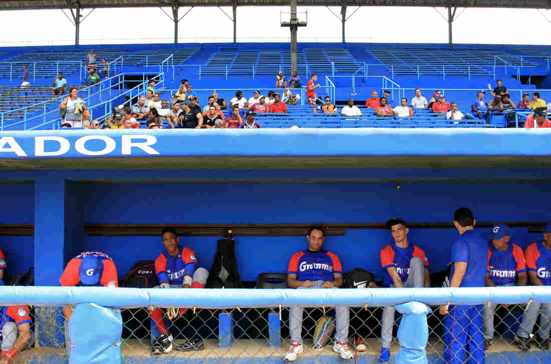 Players for the Alazanes de Granma sit in the dugout at Latin American Stadium.