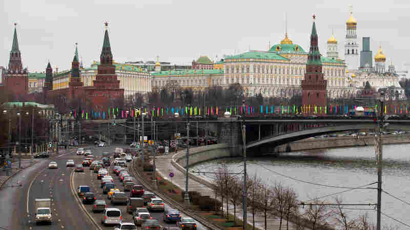 Cars drive past the Kremlin along the Moscow River last December. Foreign automakers had been ramping up production in Russia, but the country's economic woes have caused car sales to drop sharply. Several foreign automakers have cut back production, and General Motors is pulling out of Russia.