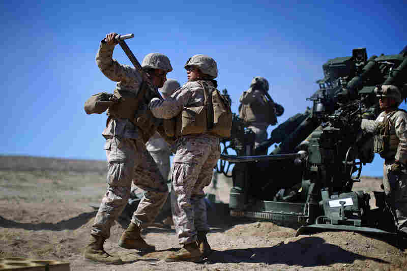 Carolina Ortiz moves away from a 155 mm artillery piece after loading it during a live-fire exercise at the Marine base in Twentynine Palms, Calif. The Marine Corps is trying to determine whether women can serve in ground combat jobs: artillery, armor and infantry. Alpha Company is undergoing training in the Mojave as part of a months-long experiment to figure that out.