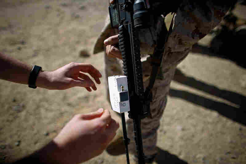 A Marine places a testing device on the barrel of a weapon before a live-fire exercise.