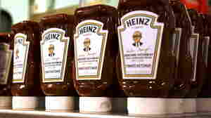 Commemorative ketchup bottles with portraits of Warren Buffett are seen at the exhibition of Berkshire Hathaway companies at the annual meeting in Omaha, Neb., on May 3, 2014. Kraft Foods said it will merge with ketchup maker H.J. Heinz Co., owned by 3G Capital and Berkshire Hathaway Inc, to form the world's fifth-largest food and beverage company.