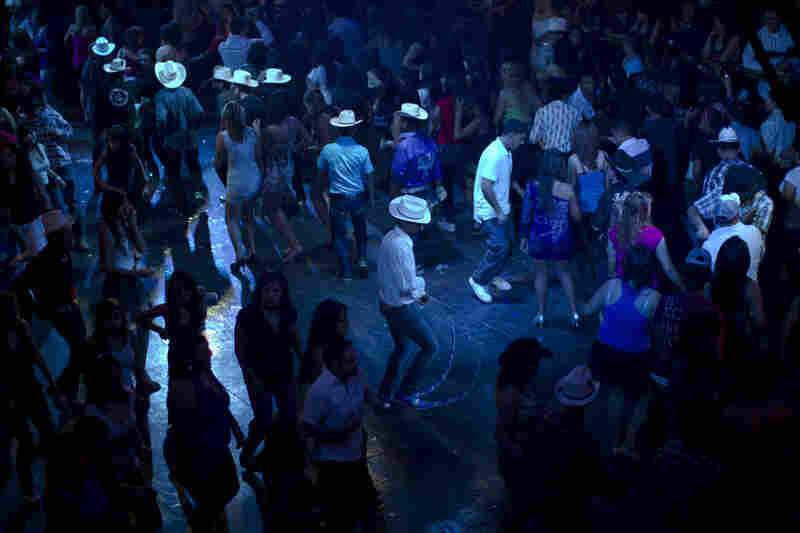 A man wears long pointy boots as he dances at a Matehuala nightclub.