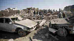 People search for survivors under the rubble of houses destroyed by Saudi airstrikes near Sanaa Airport, Yemen, on Thursday.