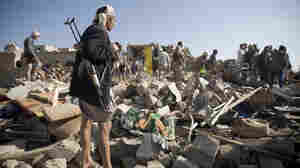 A Houthi Shiite fighter stands guard as people search for survivors under the rubble of houses destroyed by Saudi airstrikes near Sanaa airport in Yemen on Thursday.