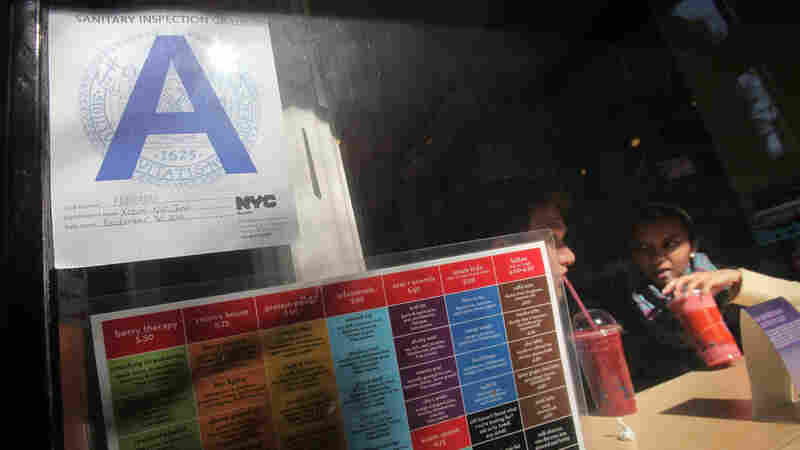 A health inspection grade is posted outside a Manhattan eatery. In several cities, Yelp users can now find out how a restaurant scored on its health inspection well before they walk through the door.