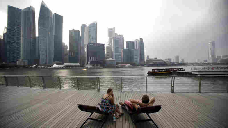 A couple enjoys the view of Singapore's financial center. Conservatives saw Singapore as a free-market success story, but Lee Kuan Yew's government played a big role in the economy.