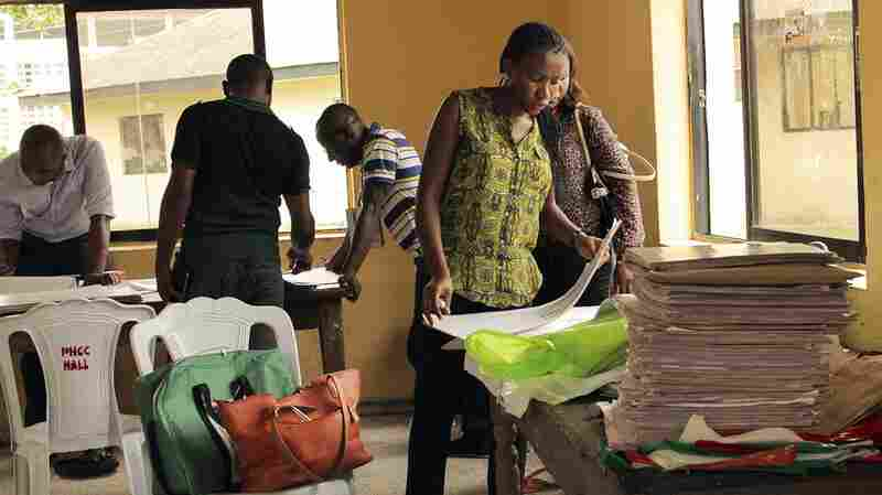Nigerian electoral officials collate results at a polling station in the oil rich Niger Delta, Port Harcourt, Nigeria on Sunday. Millions of voters headed to the polls in the Nigerian general elections after being delayed for over a month.