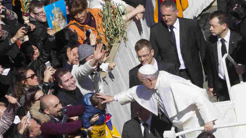 Pope Francis blesses a baby after celebrating a Palm Sunday Mass in St. Peter's Square at the Vatican.