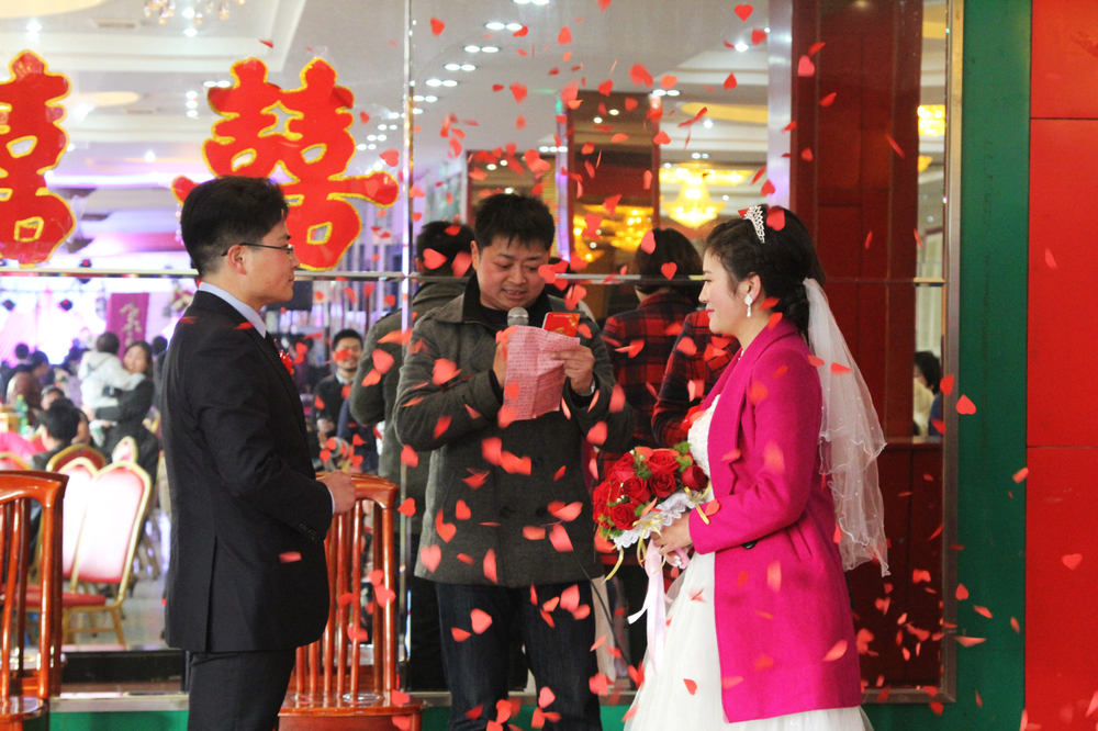 Charles and Xiao Fang stand amid a flurry of confetti during their wedding ceremony, held at a restaurant in central China.