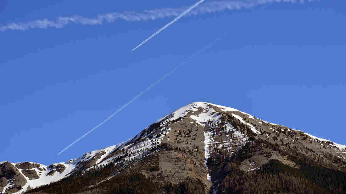 Airplanes' contrails streak the sky close to where a Germanwings plane crashed last week, in Seyne les Alpes, France.