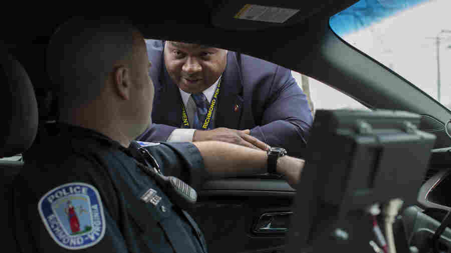 """Det. Mark Williams (center), speaks with an officer in Fairfield Court in Richmond, Va. A decade ago, amid a surge in violent crime, police were identifying relatively few murder suspects. So the police department refocused its efforts to bring up its """"clearance rate."""""""