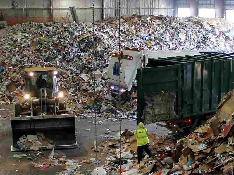 "Trucks dump their loads of single-stream recycling on the ""tip floor"" at Resource Management's MRF in Earth City, Mo."