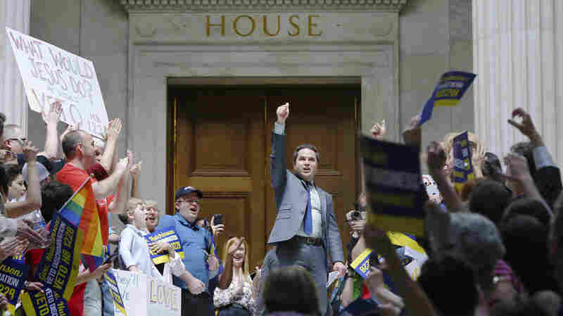Rep. Warwick Sabin, D-Little Rock (center), leads protesters outside the House chamber at the Arkansas Capitol in Little Rock on Monday.
