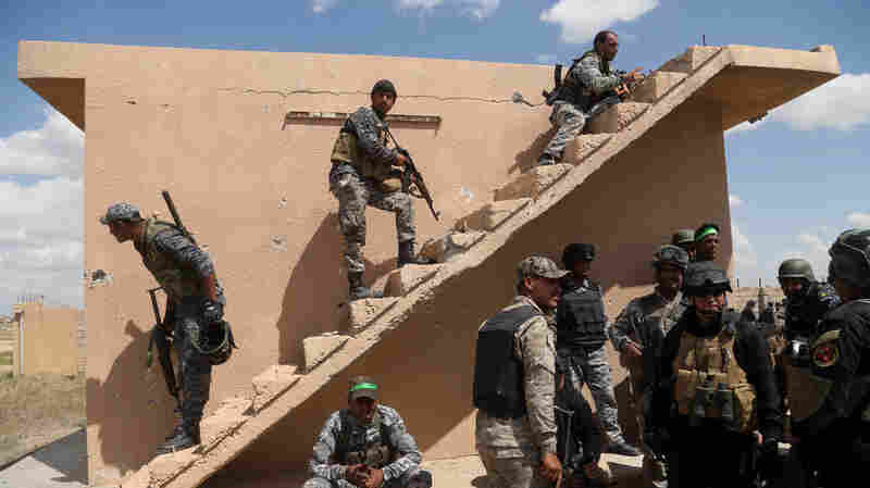 Iraqi security forces and allied Shiite militiamen look for Islamic State extremists in Tikrit on Tuesday. Iraqi forces were going house-to-house Tuesday in search of snipers and booby traps.