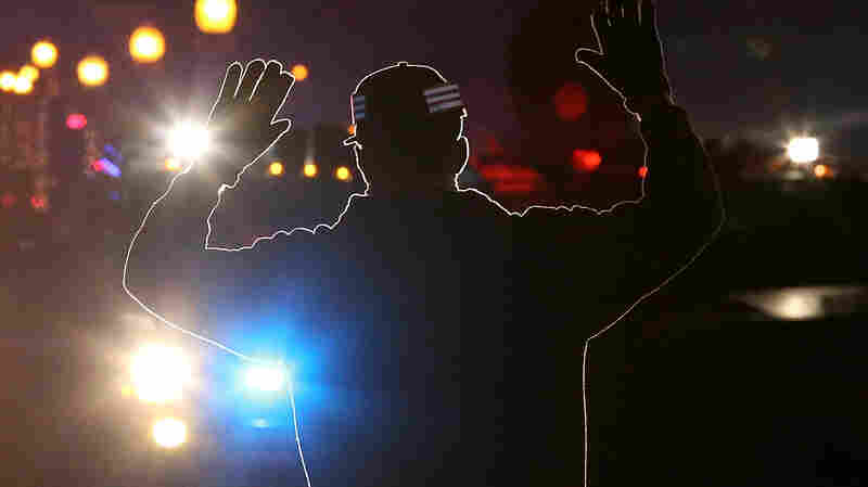 A protester stands in front of police vehicles with his hands up during a demonstration in Ferguson, Mo., where in August 2014 a white police officer shot and killed an 18-year-old black man.