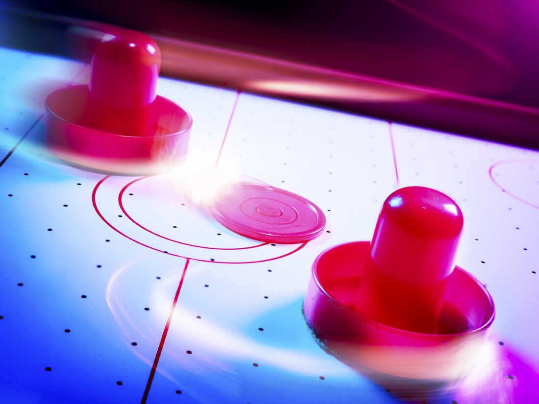 Air hockey table with dramatic lighting and motion trails