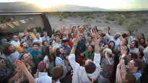 Wilderness Torah festival attendees take their Shabbat celebration outside the Tent of Meeting (at left) as the sun sets in the Panamint Valley of the Mojave Desert in 2014. At center in white, with both arms reaching up to the sky, is singer-songwriter Mikey Pauker. Shabbat participants are singing, drumming and playing guitars.