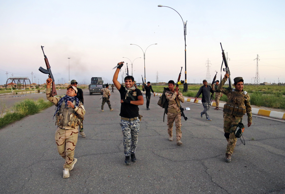 Iraqi security forces denounce the self-proclaimed Islamic State group as they open the main road between Baghdad and Tikrit on Wednesday. Many members of the Iraqi security forces and allied militiamen are Shiite Muslims, while residents of Tikrit are overwhelmingly Sunni.