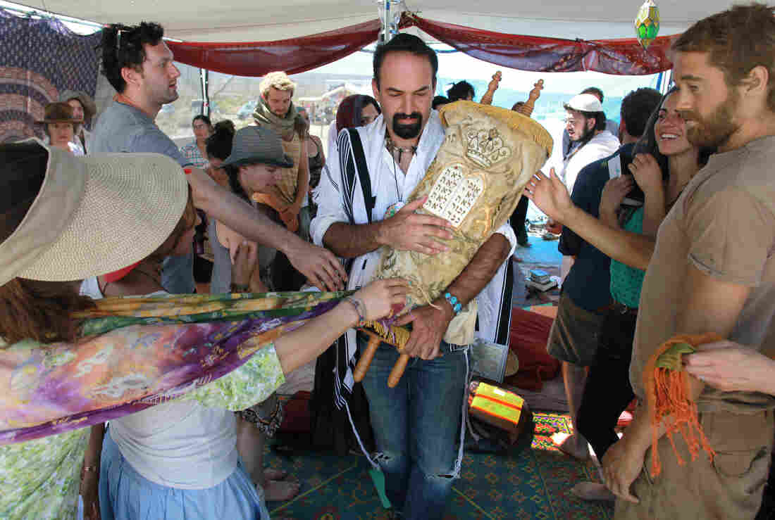 During a Saturday morning Shabbat service, Sagi Salomon carries a Torah scroll that survived the Holocaust through the Tent of Meeting. Touching the Torah cover appropriately is a symbolic way to show respect and affection for the Torah and the Jewish teachings it contains and represents.