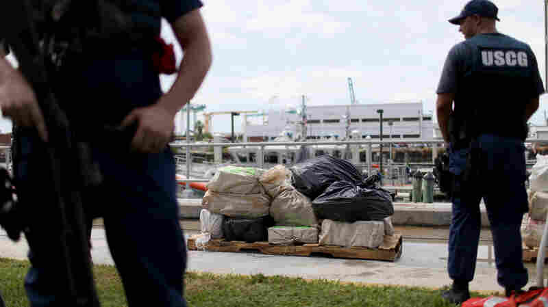 U.S. Coast Guard members stand near bags containing approximately 719 kilograms of cocaine in Miami Beach.
