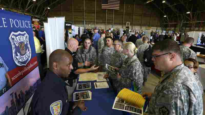 Seattle Police Detective Kevin Nelson (left) talks with U.S. Army soldiers at an October job fair at Joint Base Lewis-McChord, Wash., for soldiers who may exit military service in the next year.
