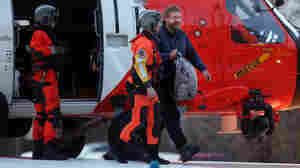 Louis Jordan (right), walks from the Coast Guard helicopter to the Sentara Norfolk General Hospital in Norfolk, Va., after being found off the North Carolina coast, on Thursday. His family says he sailed out of a marina in Conway, S.C., on Jan. 23, and hadn't been heard from since.