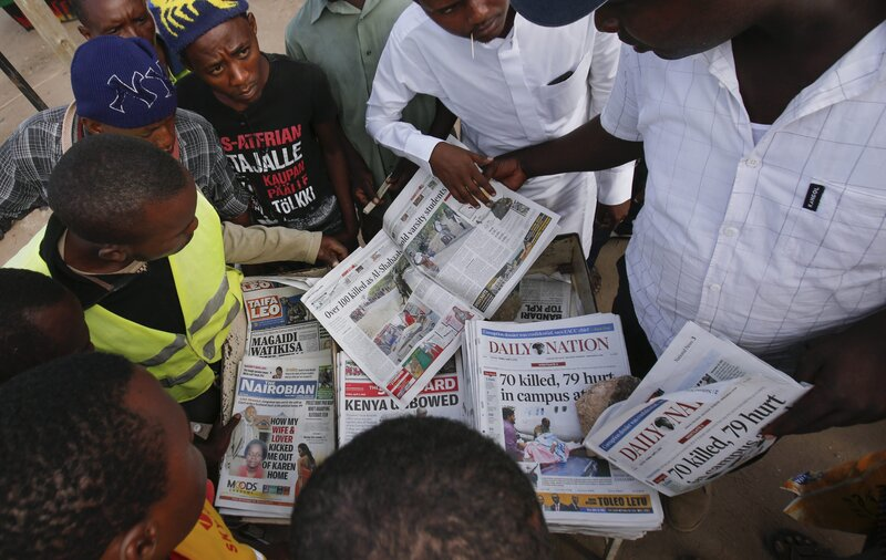 Local residents gather around a newspaper vendor to read articles on an attack on Garissa University College in Garissa town Friday.