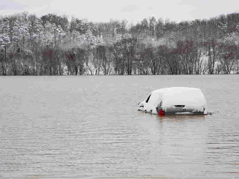 An abandoned vehicle is partially submerged along Pompeii Road after the Red River flooded some of the land surrounding Clay City, Ky., on Thursday.