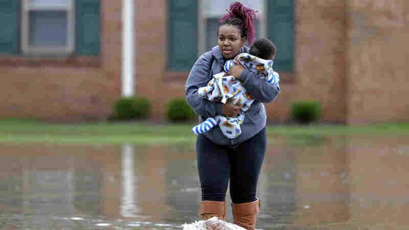 Simone Wester and her 7-month old son Jeremiah walk through the flood waters outside her apartment building at the Guardian Court Apartments in Louisville, Kentucky, on Friday.