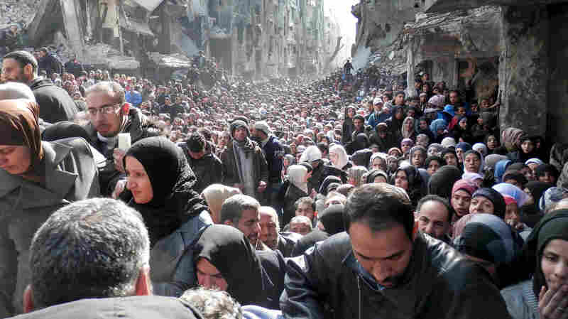 A photo taken in January 2014 and released by the United Nations Relief and Works Agency for Palestine Refugees (UNRWA), shows residents of the besieged Palestinian camp of Yarmouk, queuing to receive food supplies, in Damascus, Syria.