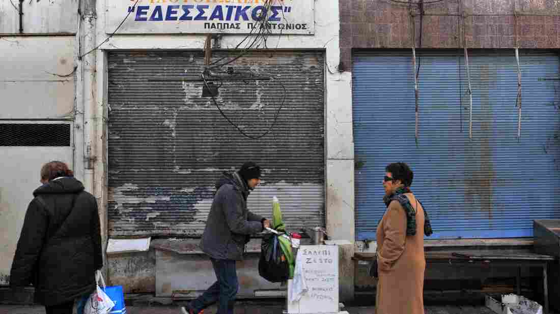 People walk by closed shops in Thessaloniki in March. Greece, though it has once again averted bankruptcy, is still struggling economically.