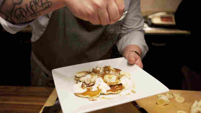 Voltaggio sprinkles sugar on granola pancakes, a dish from his new cookbook, Home.